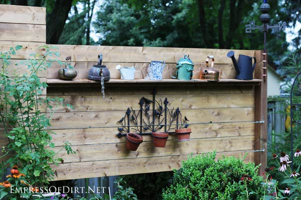 Collection of kettles on garden fence.