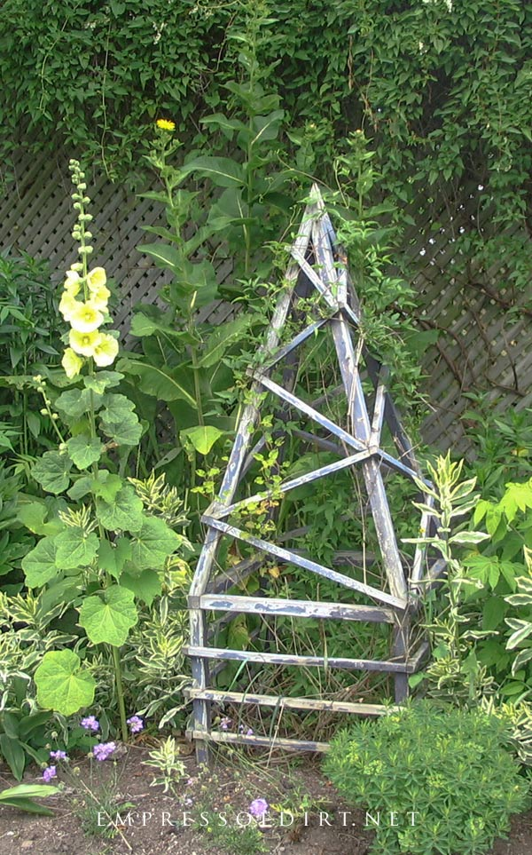Old-fashion garden obelisk with wide base.