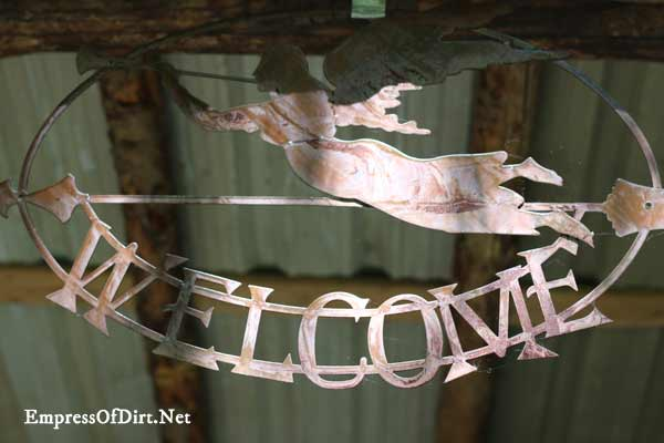 Rusty welcome sign hanging from garden shed.