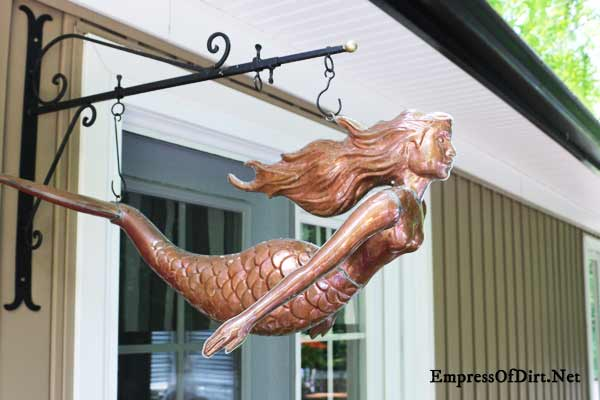 Rusty mermaid as garden art.