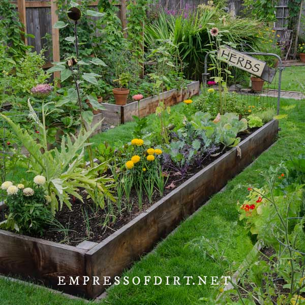 Raised garden bed with vegetables and flowers and an old garden gate with a sign saying Herbs.