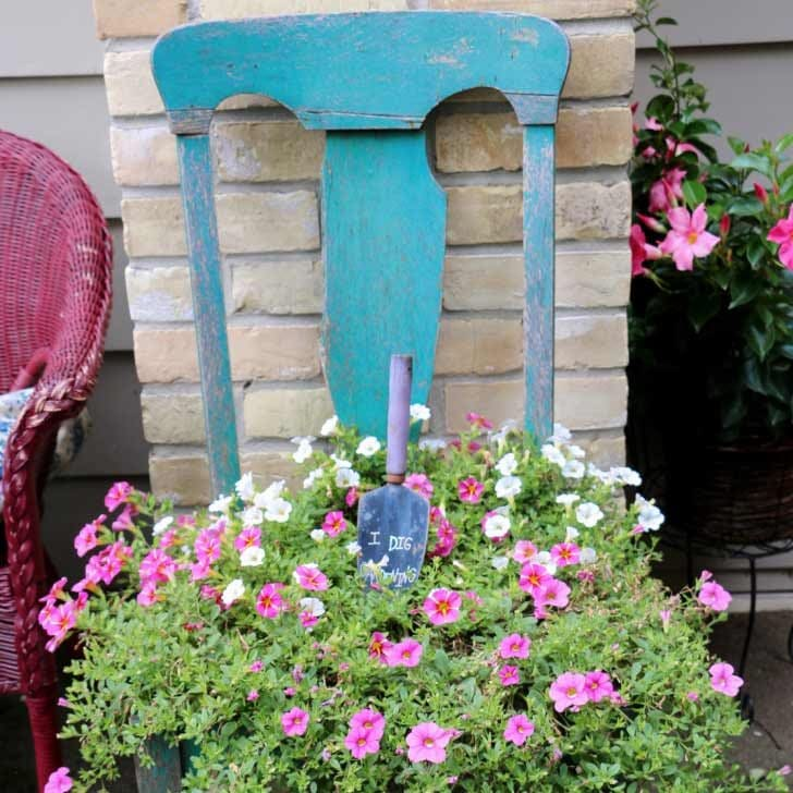 Old blue kitchen chair used as a plant stand.