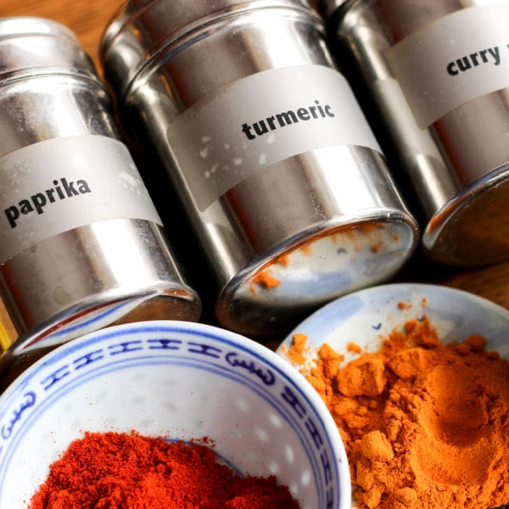 Curry powder, turmeric, and paprika in bowls with labelled containers.
