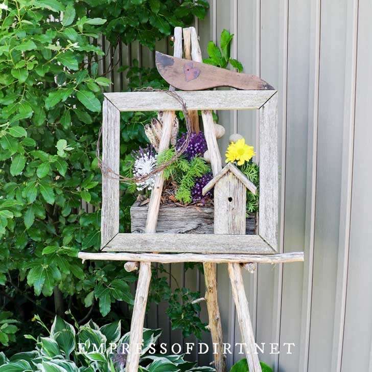 Closeup of outdoor easel with picture frame and birdhouse.