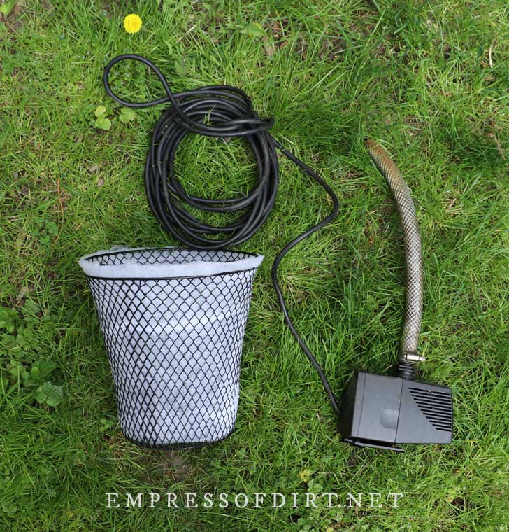 Two mesh baskets sandwiching quilt batting and a pond pump.