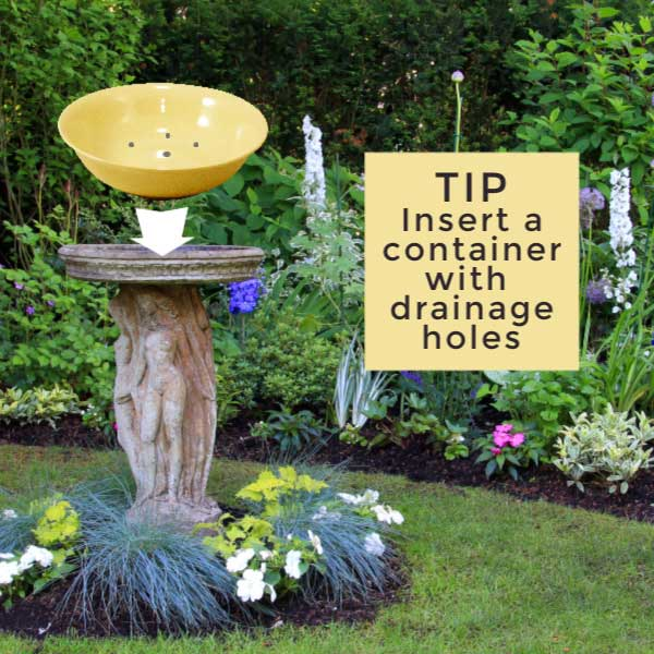 Photo of birdbath with plastic bowl on top.