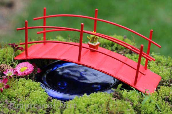 Red miniature bridge over faux water in fairy garden.
