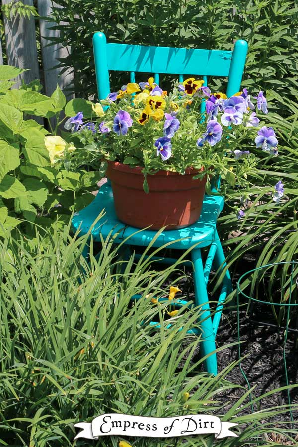 Turquoise wooden kitchen chair with flower pot
