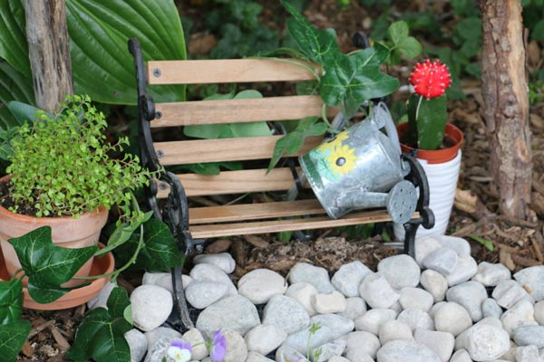 Watering can used as fairy garden fountain.