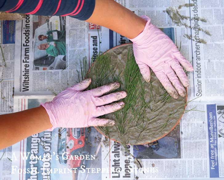 Hands adding leaves to a DIY fossil imprint stepping stone from the book, A Woman's Garden by Tanya Anderson.
