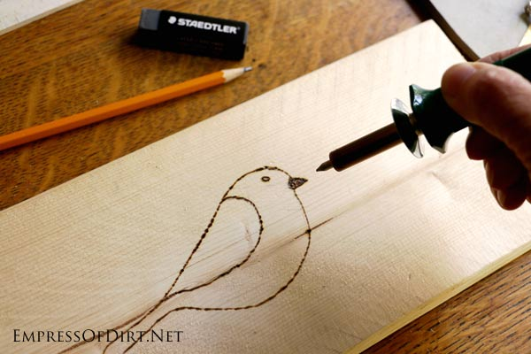 Creating a simple bird design on wood with a wood burning tool.