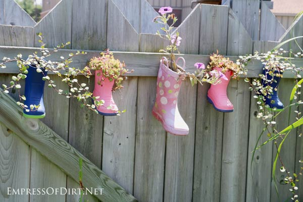 Children's rubber boots used as hanging planters on fence.