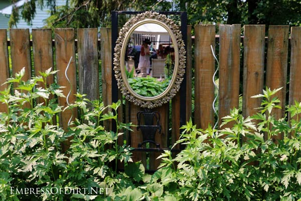 Fancy mirror hanging on fence.