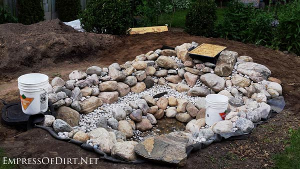 Placing stones and gravel in a backyard pond.