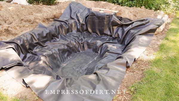 Adding liner to garden pond.