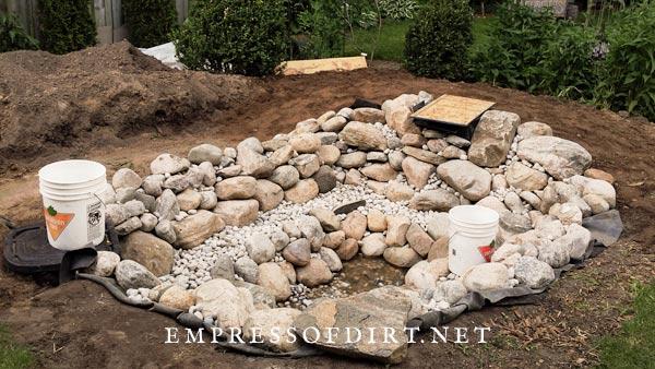 Adding stones to garden pond.