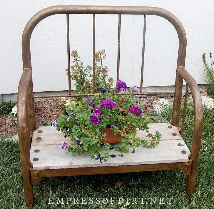 Garden bench made from old metal bed frame.