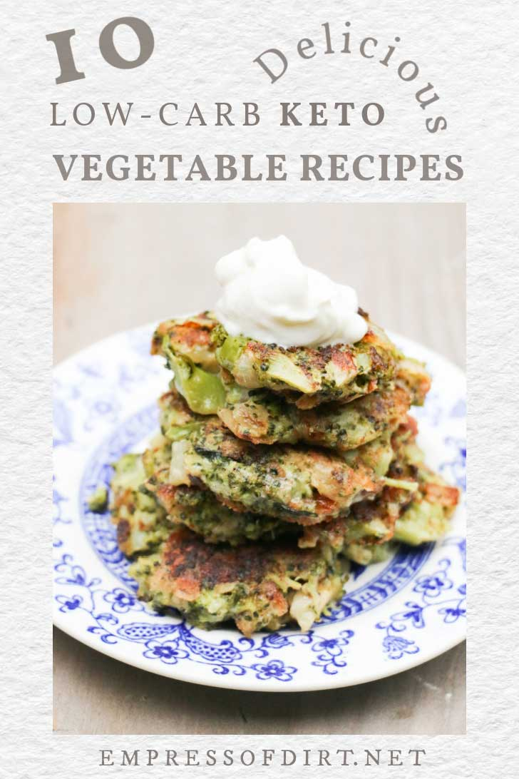Low-carb zucchini fritters stacked on a plate with sour cream on top.