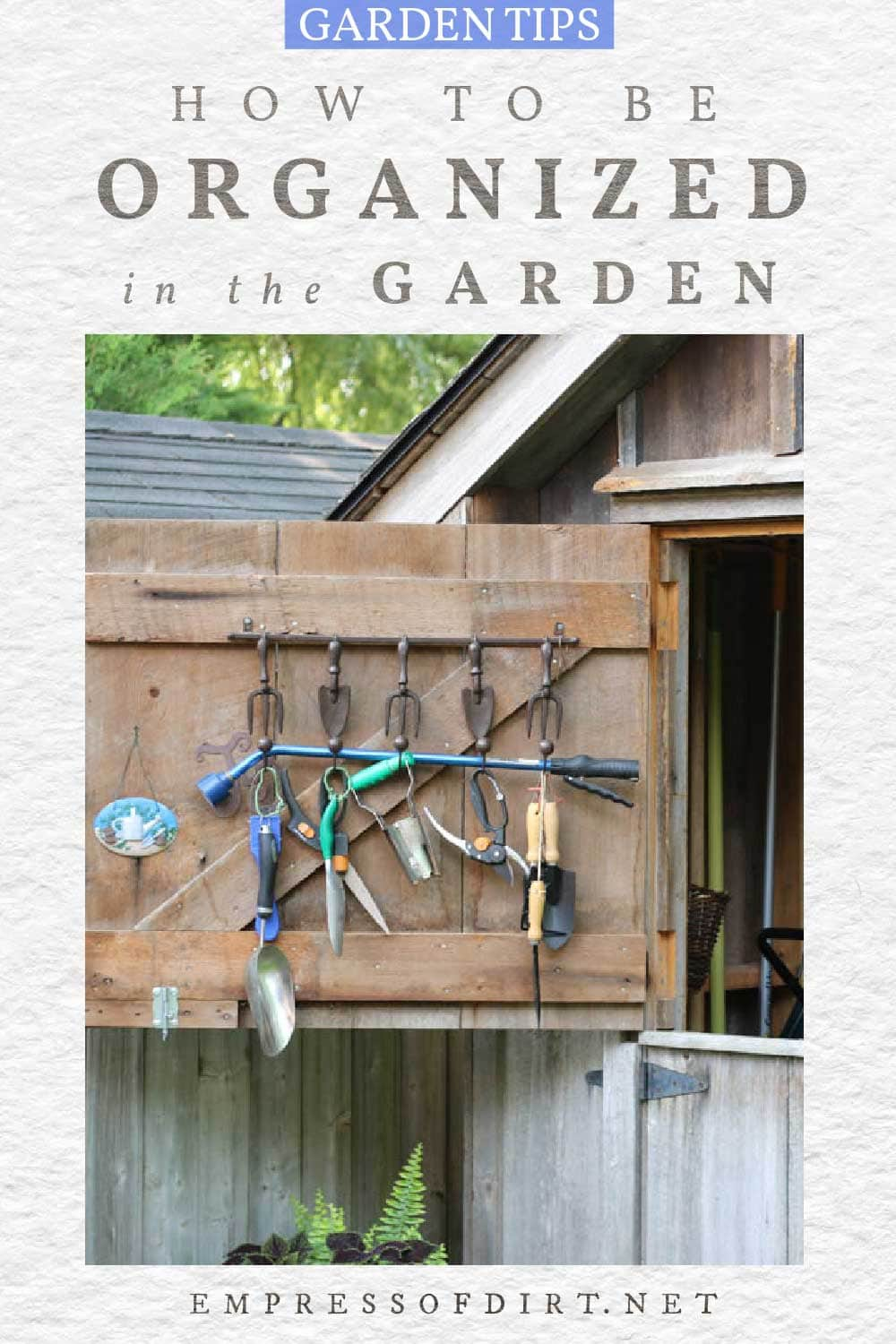 Garden tools hanging on the door of a shed.