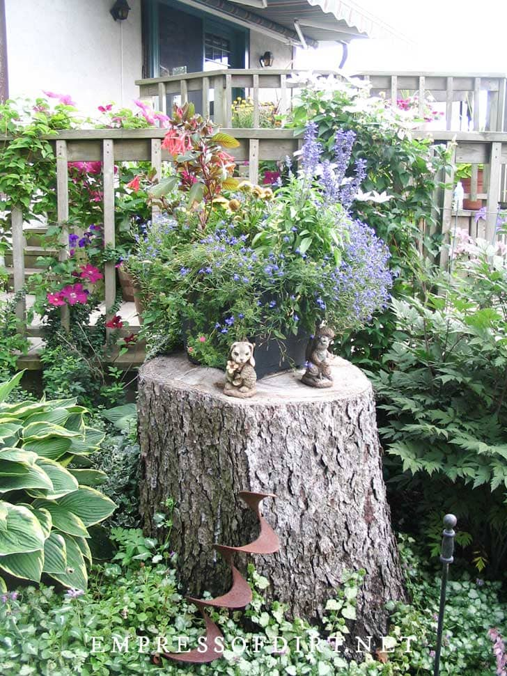 Old tree stump used as a flower planter stand in a garden.