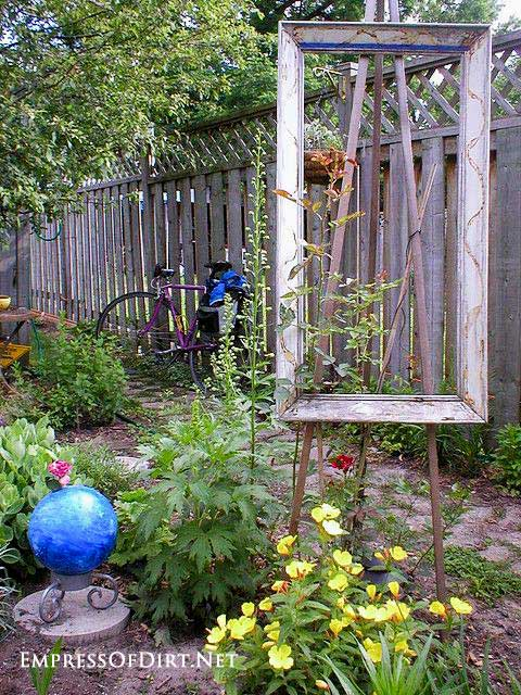 Simple outdoor easel in garden with blue gazing ball.