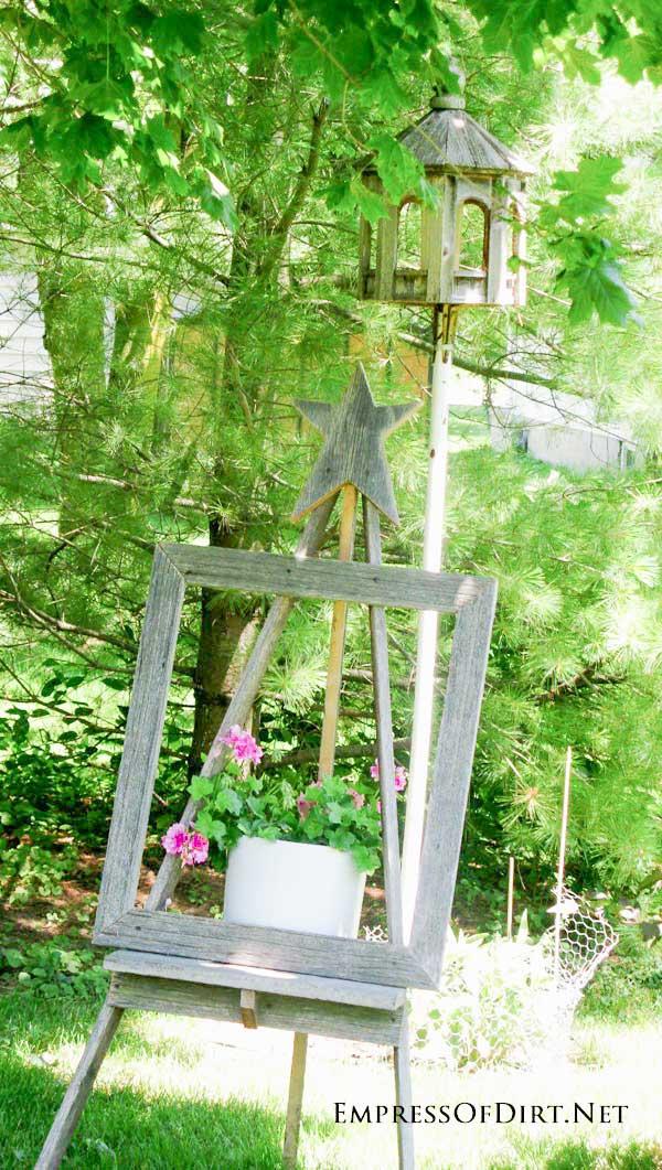 Plain garden art easel with pink flowers.