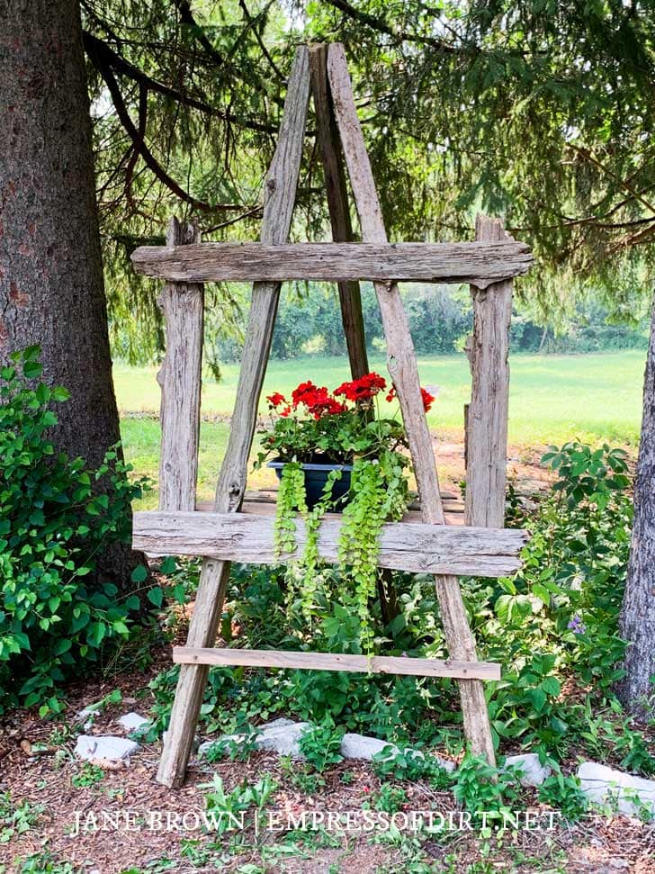 Rustic garden easel with red geraniums.