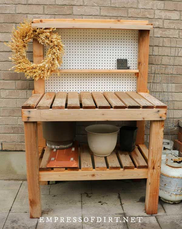 Wood potting bench with slat top.