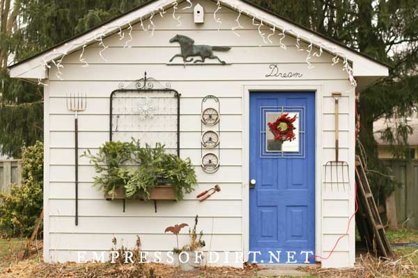 Garden shed decorated with art and old metal gate.