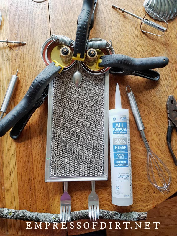 Gluing owl garden junk with adhesive and clamps.