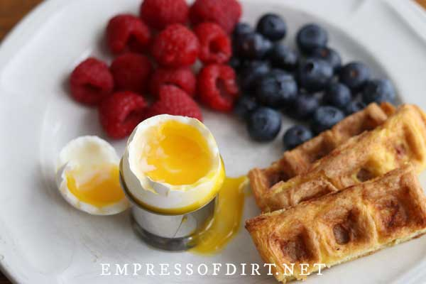 Soft boiled egg, berries, and chaffle slices.