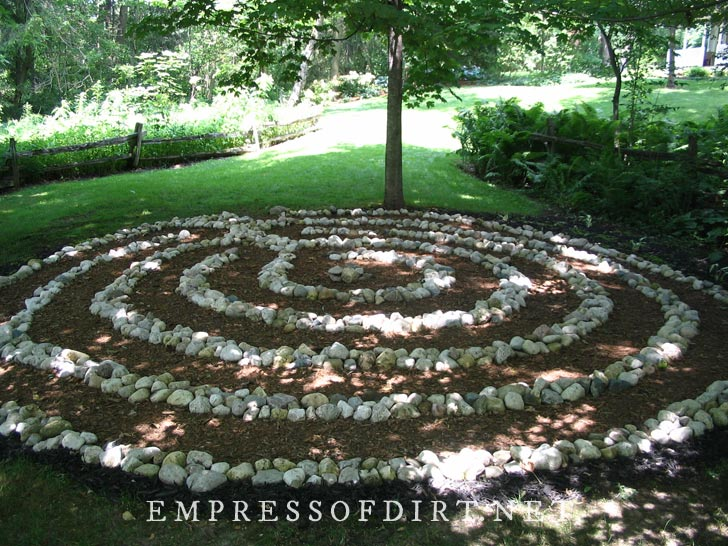 Circle of stones in a shady garden with trees.