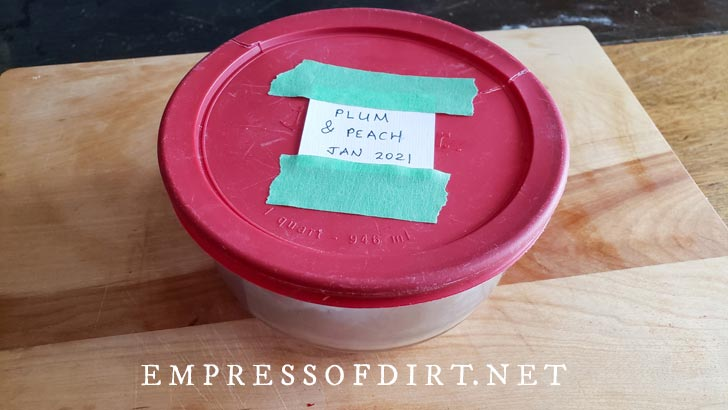 Glass food container with label on lid listing plum and peach pits inside.