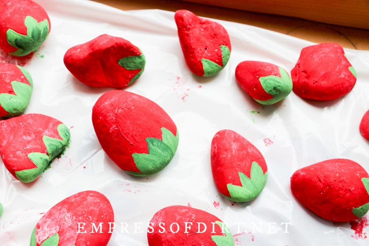 Stones painted to look like strawberries with green leaves and red berries.