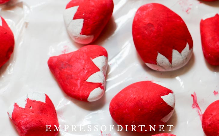 Stones with red and white paint in the process of painting strawberries.