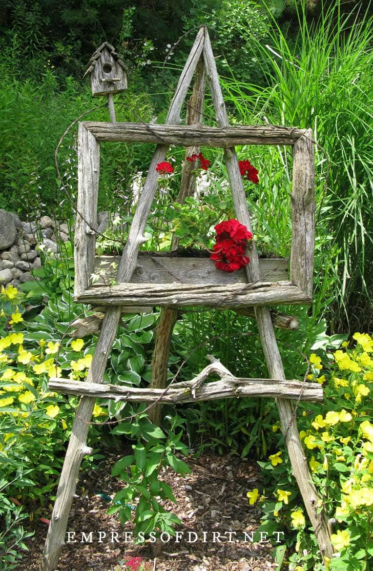 Rustic garden art easel with red geraniums.