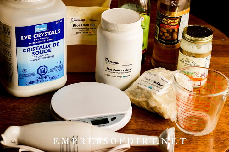 Soapmaking supplies including lye, digital scale, hand blender, and measuring cups.