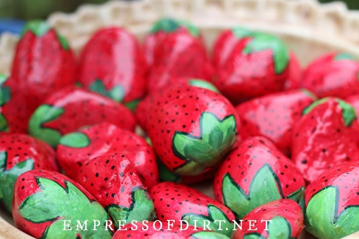 Bowl of stones painted to look like strawberries.