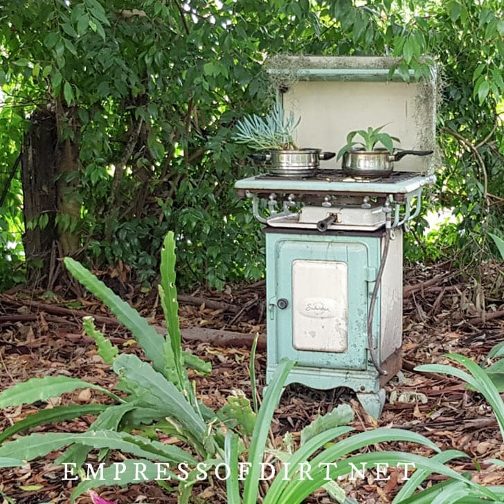 Antique cookstove in garden planted with succulents.