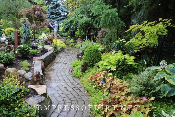 Winding brick path through lush garden.