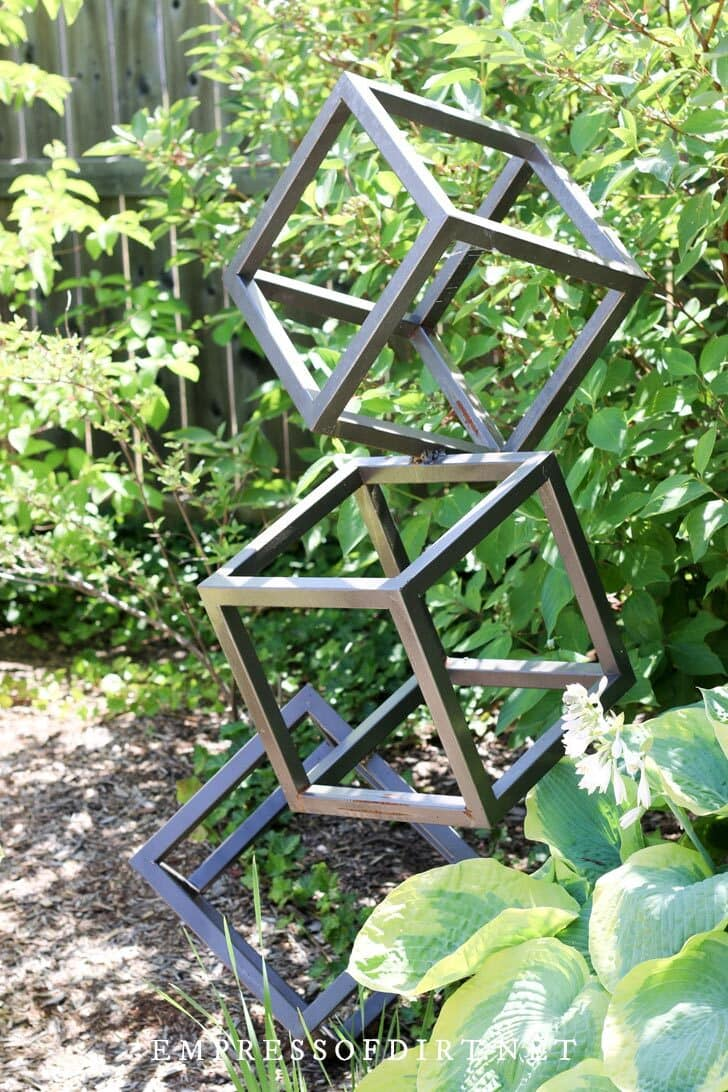 Modern garden art of stacked metal boxes.