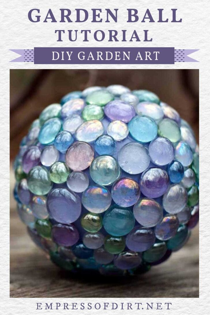 Decorative garden art ball in shades of blue, pink, and green.
