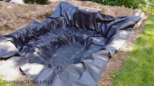 Adding a liner for a backyard garden pond.
