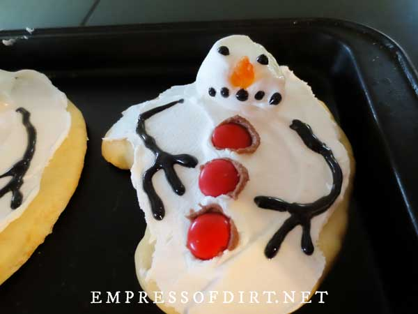Melted snowman cookie with red candy buttons.