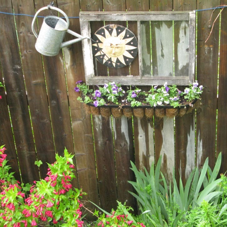 Inexpensive garden art including a window and watering can hanging on a fence.