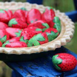 Stones handpainted to look like strawberries.
