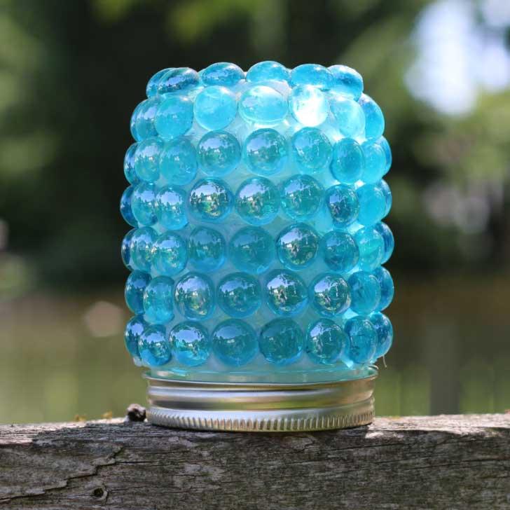 Garden art treasure jar with glass gems.