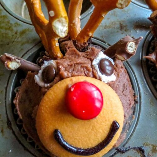 Chocolate cupcake with a face that looks like a reindeer made from cookies, pretzels, and candies.