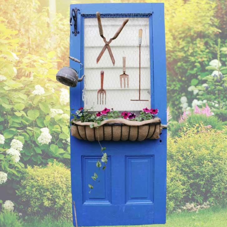 Blue farmhouse doors decorated with garden art.
