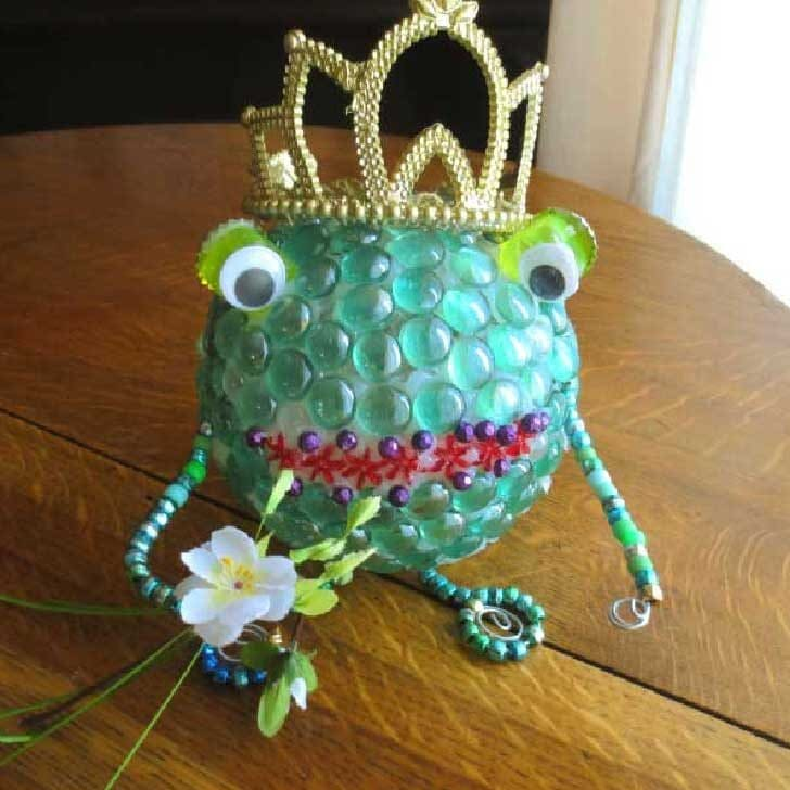 Garden art frog prince with crown; made from glass gems.
